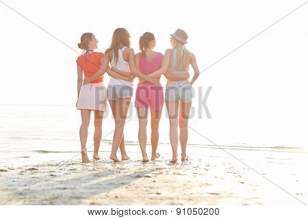 summer vacation, holidays, travel, friendship and people concept - group of young women walking on beach