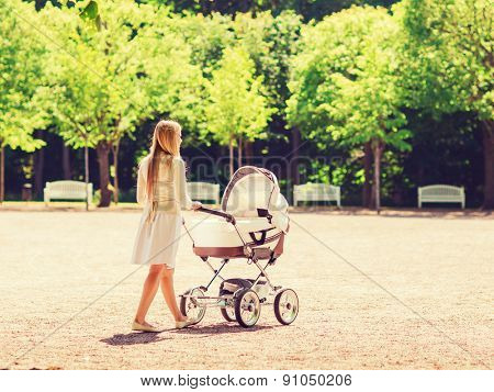family, child and parenthood concept - happy mother walking with baby stroller in park from back