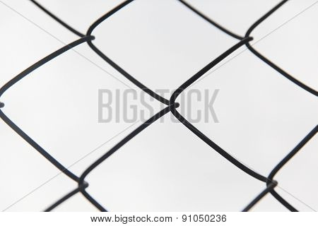 captivity, prison and obstruction concept - close up of mesh fence over gray sky