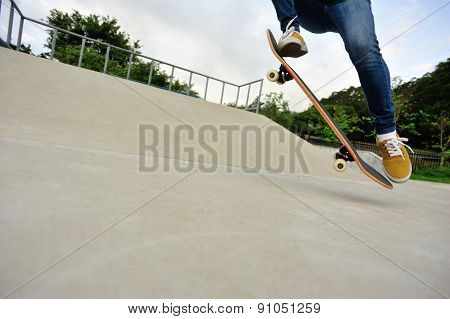 skateboarding legs doing trick ollie at skatepark