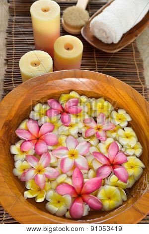 wooden bowl in many frangipani with spa set on mat