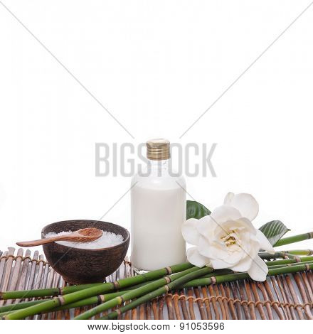 Set of massage oil and fern, grove ,salt in bowl on bamboo mat