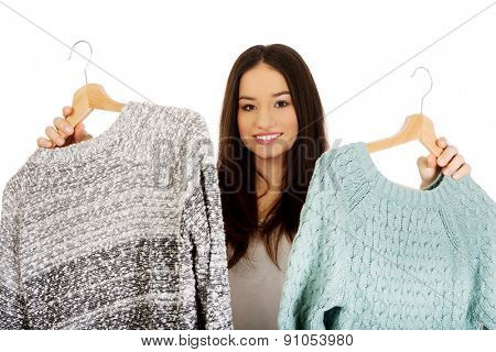 Teen with two sweaters thinking what to dress.