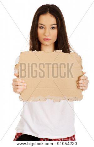Teenage woman holding empty cardboard.