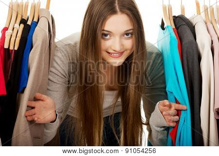Happy teen woman between clothes on hanger.
