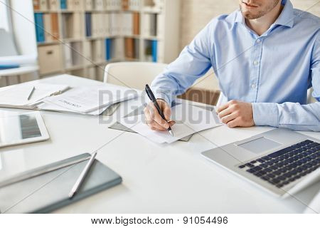 Businessman with pen writing down his ideas on paper