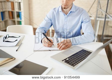 Serious young man writing down his ideas on paper