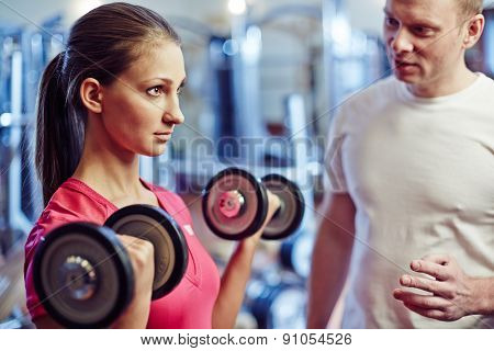 Portrait of young woman exercising with barbells in gym