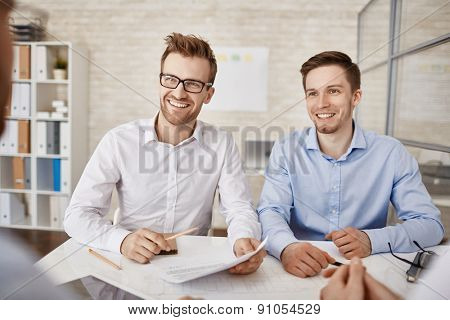 Two successful businessmen consulting colleagues in office
