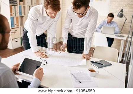 Elegant architects discussing blueprint in working environment