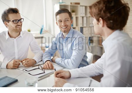 Group of handsome employees discussing plans in office