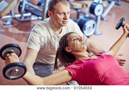 Sporty girl training in gym with her trainer helping her