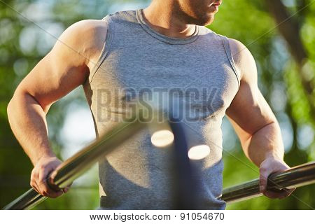 Active man in grey vest doing exercise for arms outdoor