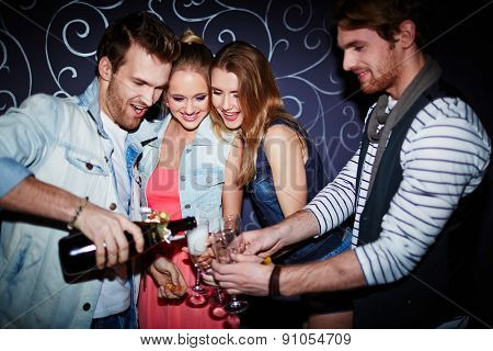 Happy guy pouring champagne in flutes of friends at party