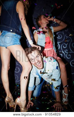 Ecstatic guy having fun with girls in night club