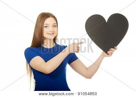 Beautiful teenage woman pointing on paper heart.