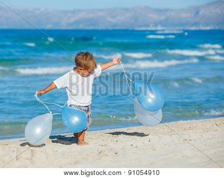 Little boy with ballons on the beach