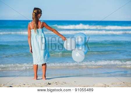 Little girl with ballons on the beach