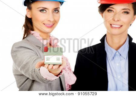 Two attractive architects women with house model.
