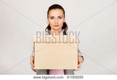 Sad businesswoman carrying box after losing job.
