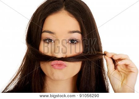 Funny teen woman putting hair like mustache.