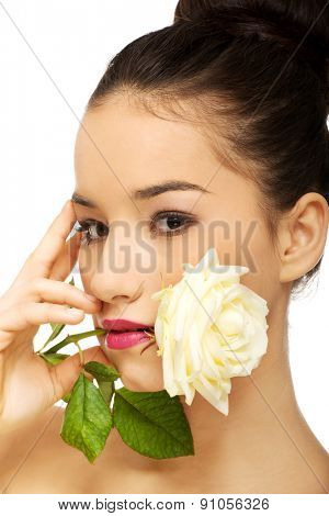 Sensual spa woman with white rose in mouth.