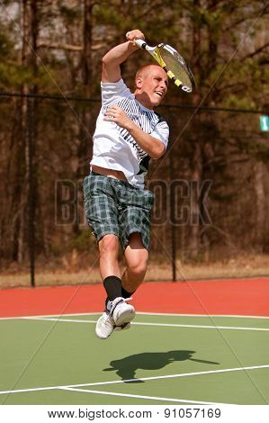 Male Tennis Player Follows Through On Leaping Overhead Shot