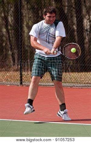 Male High School Tennis Player Hits Backhand