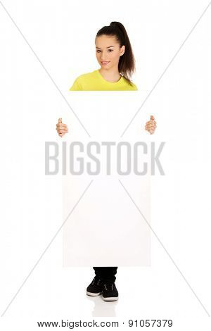 Young happy teenage woman with blank board.