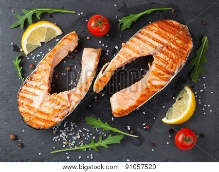 Grilled salmon and spices on stone plate. Top view