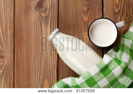 Milk cup and bottle on wooden table. Top view with copy space