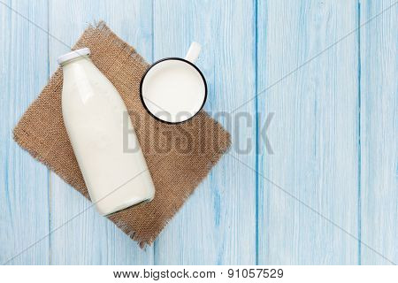 Milk cup and bottle on blue wooden table. Top view with copy space