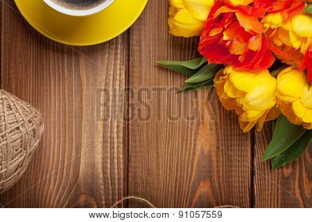 Colorful tulips bouquet and coffee cup on wooden table. Top view with copy space