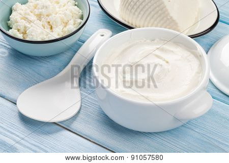 Dairy products on wooden table. Sour cream, cheese and curd