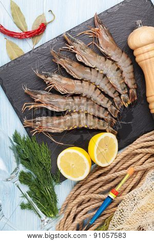 Fresh raw tiger prawns and fishing equipment on wooden table. Top view