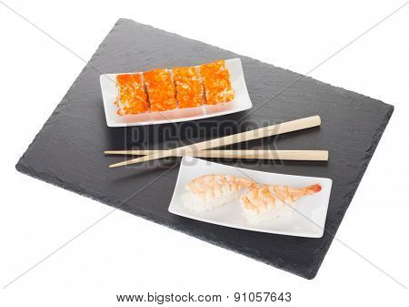 Sushi maki and shrimp sushi on black stone. Isolated on white background