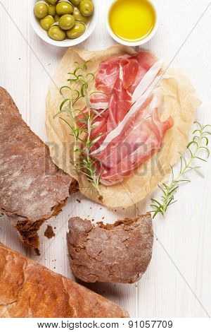 Italian prosciutto with ciabatta and olives on white wooden table