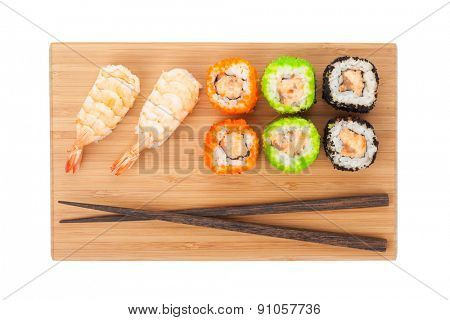 Sushi maki on bamboo board. Isolated on white background
