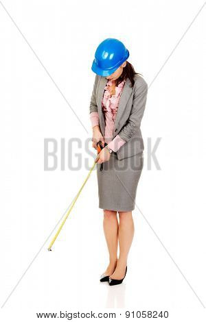 Engineer woman in suit holding tape measure in hand.