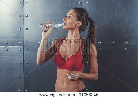 Muscular sporty athlete woman drinking water at the gym after exercising working out fitness, sport,