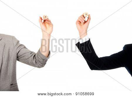 Two businesswomen holding big pencils.
