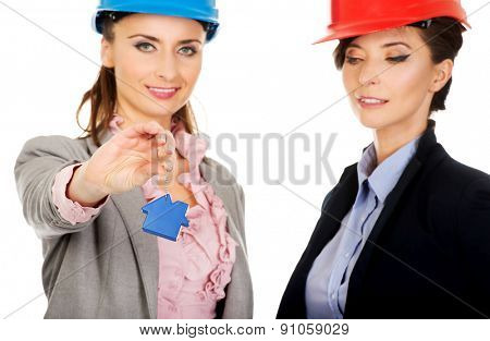 Two attractive architects women with house key.