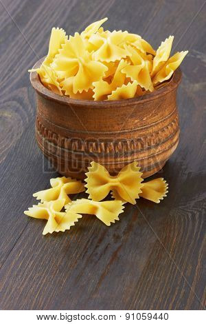 Farfalle italian pasta in wood bowl, on wood background