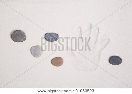 Hand print in the sand with five stones for meditation concepts.