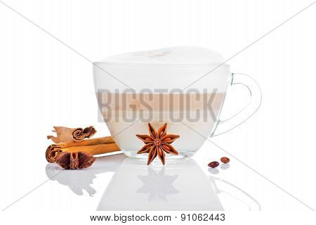 Cup of coffee latte with cinnamon sticks and star anise