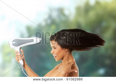 Young happy woman drying her hair.