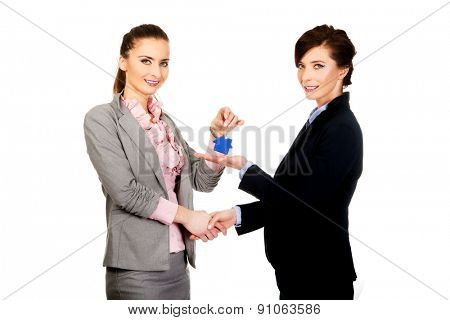 Caucasian businesswoman giving house key to her partner.
