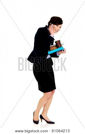 Busy businesswoman with notebooks talking on the phone.