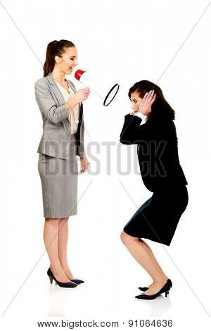 Businesswoman screaming with megaphone on her friend.
