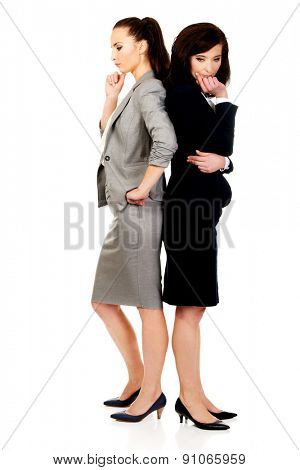 Two thoughtful businesswomen leaning on each other.